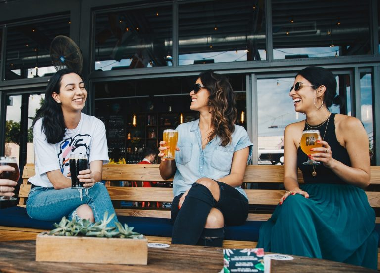 three women sitting on bench drinking beer